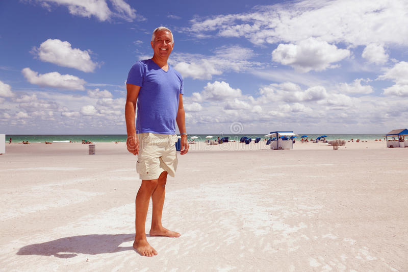 Knappe middenleeftijdsmens bij het strand stock foto