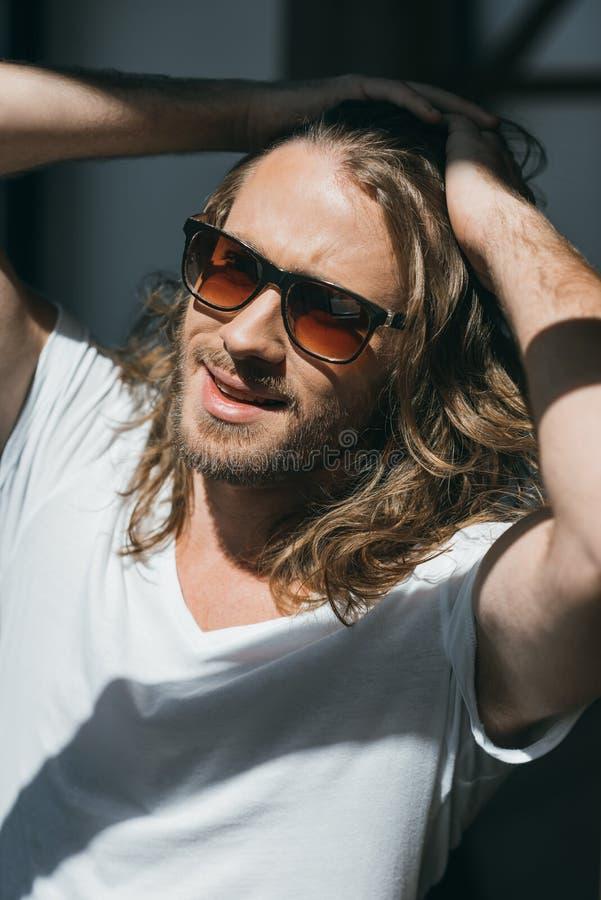 Knappe modieuze jonge mens in zonnebril die in openlucht stellen stock fotografie