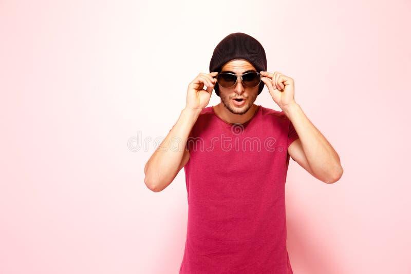 Knappe modieuze kerel in zonnebril die camera bekijken stock fotografie