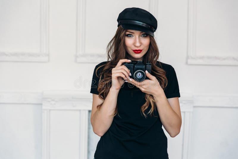 Knappe modieuze meisjesfotograaf, die een zwarte T-shirt zonder drukken, en een GLB dragen, die haar lippen met rood kleuren royalty-vrije stock foto's