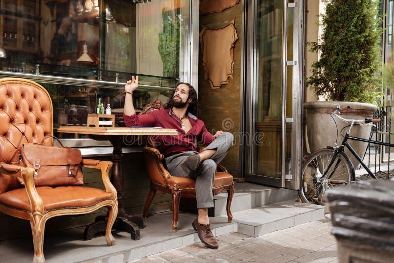 Knappe modieuze mens die op een kelner wachten royalty-vrije stock fotografie