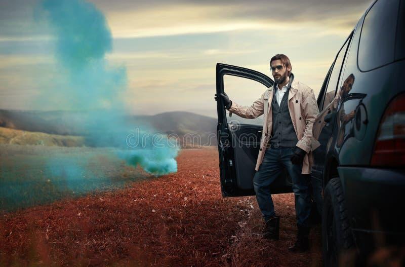 Knappe modieuze mens op de weg naast zijn auto royalty-vrije stock foto's