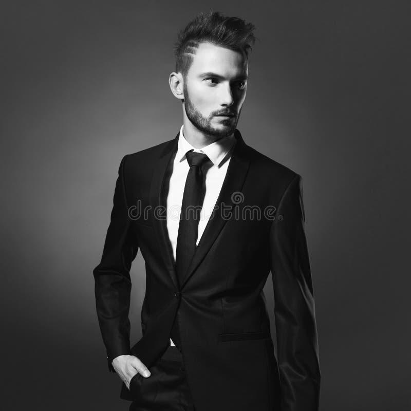 Knappe modieuze mens in zwart kostuum stock fotografie