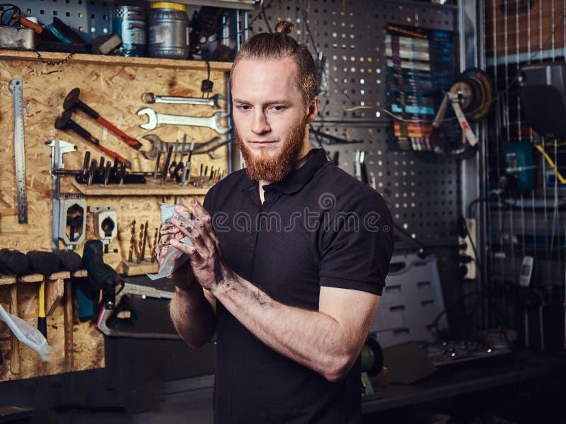 Knappe modieuze roodharigearbeider, die zijn vuile handen na herstellen schoonmaken die in een workshop werken stock fotografie