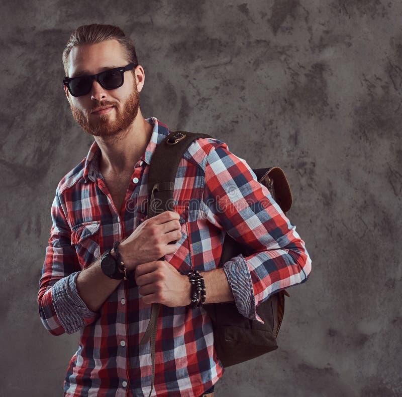 Knappe modieuze roodharigereiziger in een flaneloverhemd en zonnebril met een rugzak, die in een studio op grijs stellen royalty-vrije stock afbeelding