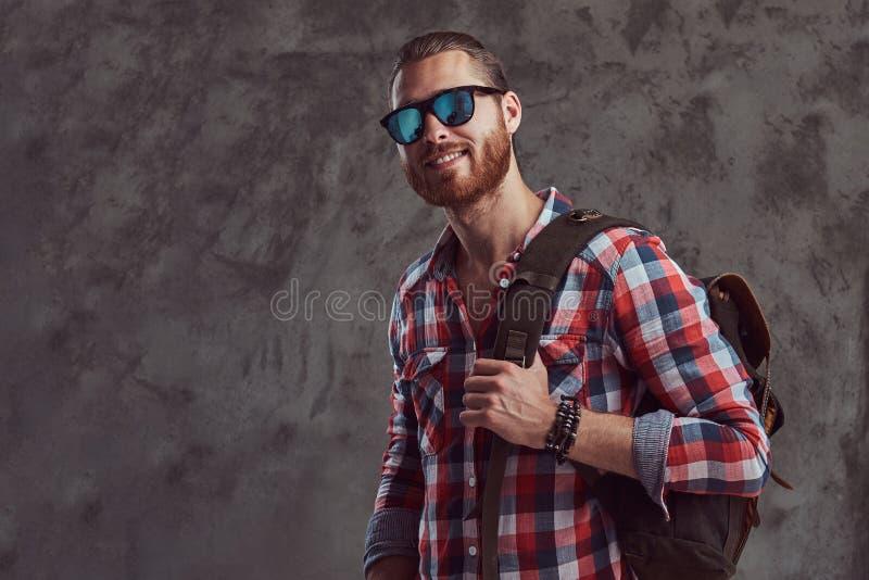 Knappe modieuze roodharigereiziger in een flaneloverhemd en zonnebril met een rugzak, die in een studio op grijs stellen stock foto