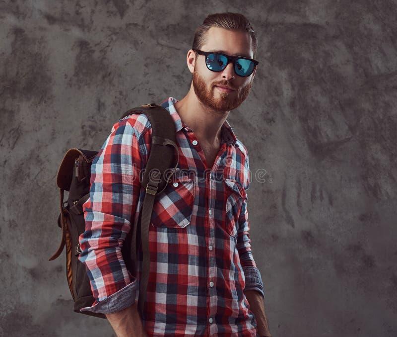 Knappe modieuze roodharigereiziger in een flaneloverhemd en zonnebril met een rugzak, die in een studio op grijs stellen stock afbeeldingen