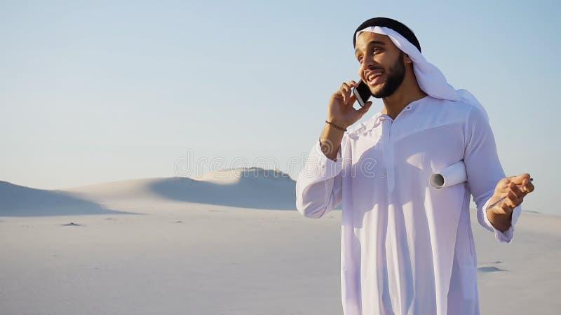 Knappe Moslim Arabische Sjeikarchitect die op mobiel spreken met stock foto's
