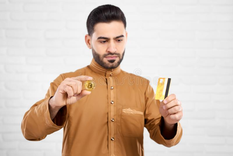 Knappe Moslim die ernstig terwijl het bekijken creditcard en het houden van gouden bitcoin zijn royalty-vrije stock afbeeldingen