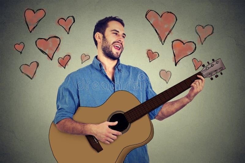 Knappe musicus jonge mens in liefde het spelen gitaar en het zingen van een lied stock foto