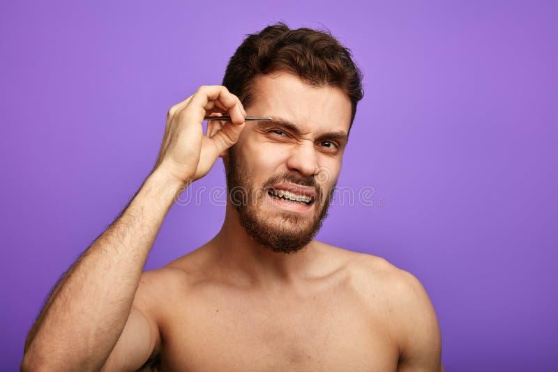 Knappe naakte kerel die zijn wenkbrauwen plukken, die negatieve emoties uitdrukken Ge?soleerd op blauwe achtergrond royalty-vrije stock afbeelding