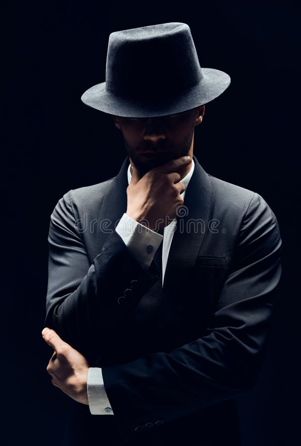 Knappe nadenkende mens in zwart kostuum en hoed wat betreft kin op donkere achtergrond stock foto's
