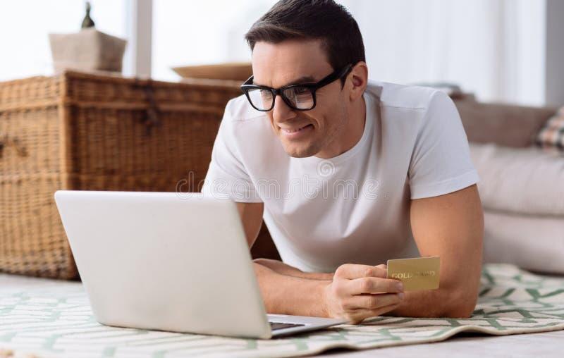 Knappe opgetogen mens die zijn creditcard gebruiken stock afbeelding