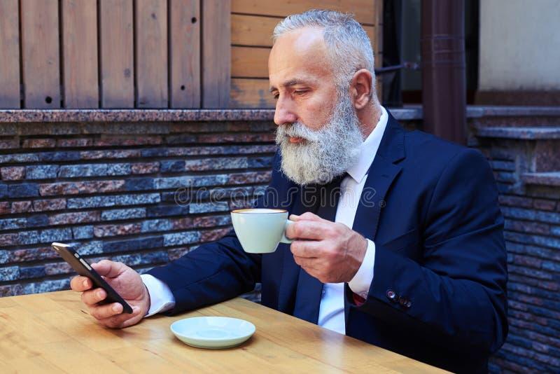 Knappe oude mens het drinken koffie terwijl het surfen in mobiele telefoon royalty-vrije stock fotografie