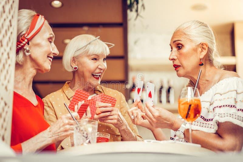 Knappe oude vrouwen die in het gokken kaartspel worden geïmpliceerd stock foto