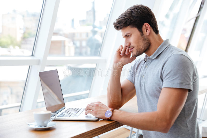 Knappe peinzende mens die met laptop werken terwijl het hebben van koffiepauze royalty-vrije stock fotografie