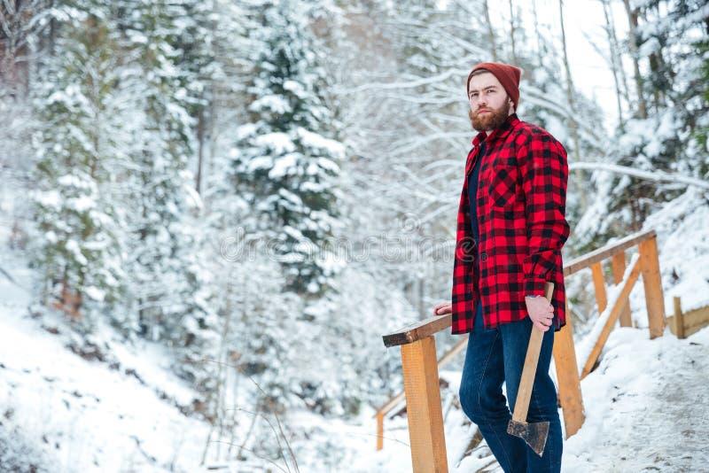 Knappe peinzende mens met bijl die zich in het bos van de bergwinter bevinden royalty-vrije stock afbeelding
