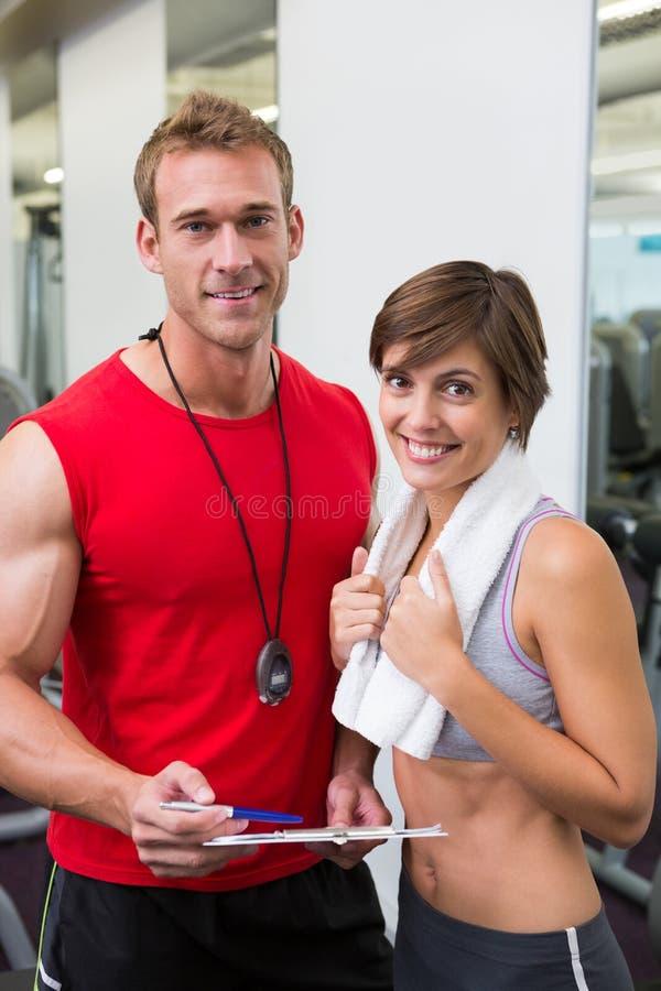Knappe persoonlijke trainer met zijn cliënt die bij camera glimlachen royalty-vrije stock foto