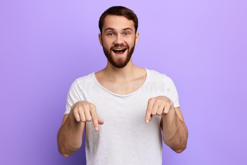Knappe positieve mens die neer met twee vingers richten royalty-vrije stock fotografie
