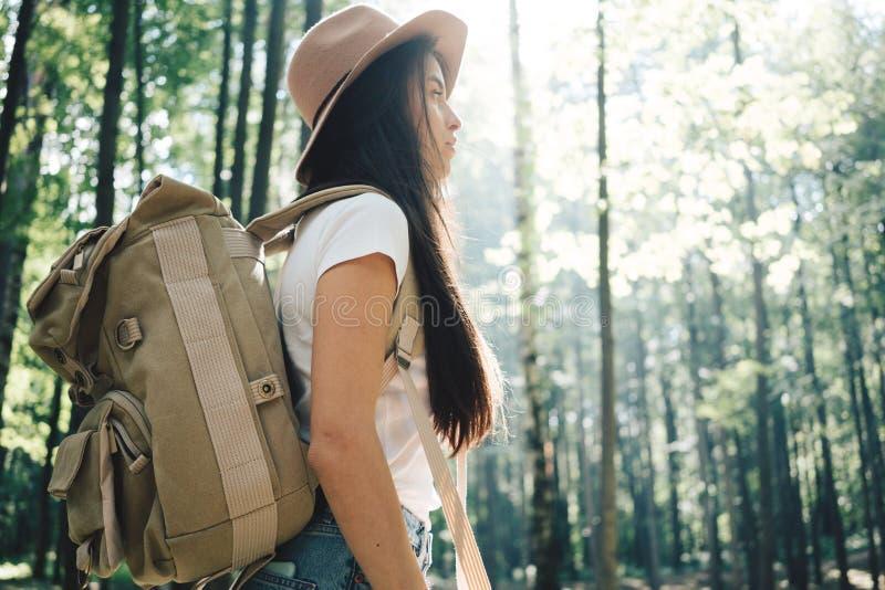 Knappe reizigersvrouw met rugzak en hoed die zich in het bos Jonge hipstermeisje lopen onder bomen op zonsondergang bevinden stock afbeelding