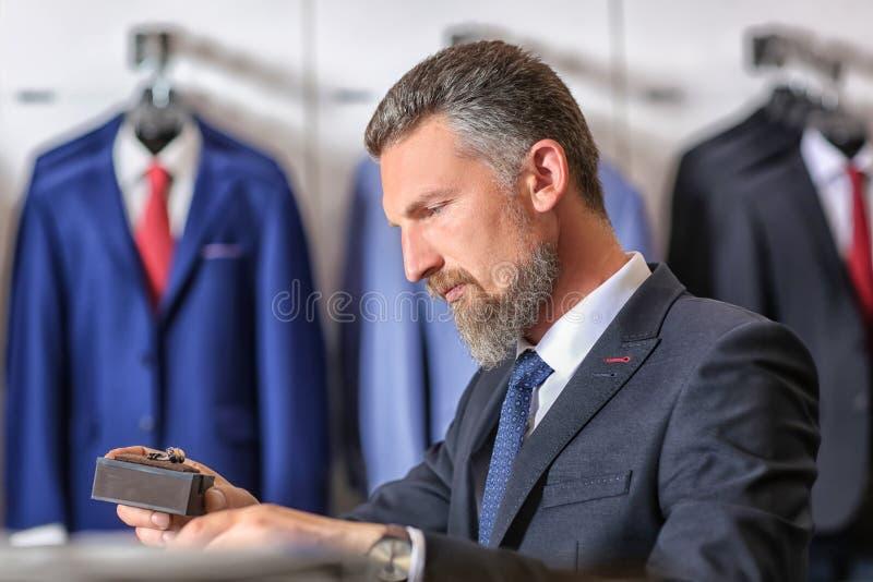 Knappe rijpe mens die toebehoren in menswear opslag kiezen royalty-vrije stock afbeeldingen
