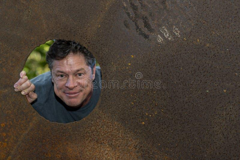 Knappe rijpe mens in het gat van de ijzerplaat, die tevreden grijnzen, gelukkig, weg eruit zien stock afbeelding