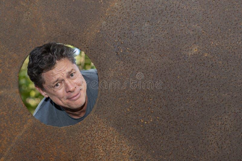Knappe rijpe mens in het gat van de ijzerplaat, die tevreden grijnzen, gelukkig, weg eruit zien stock fotografie
