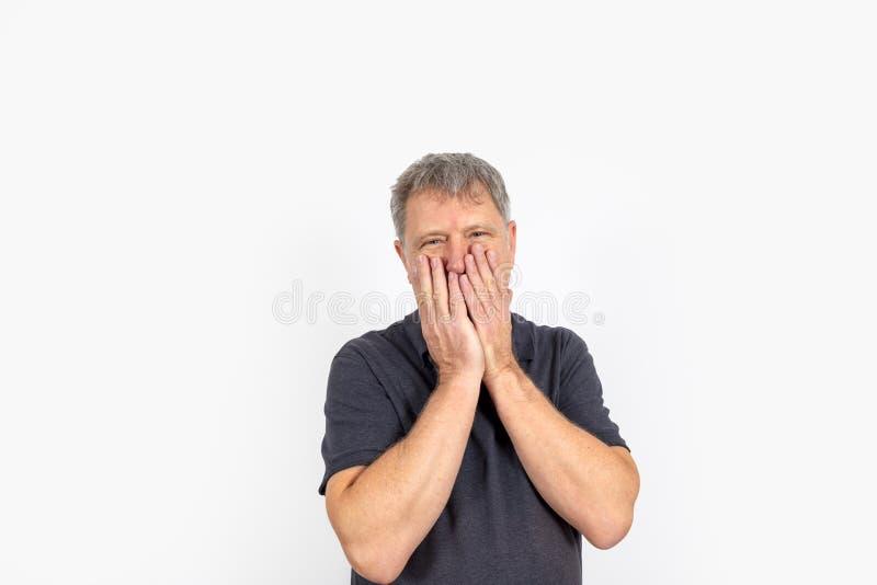 Knappe rijpe mens met handen bij gezicht royalty-vrije stock afbeeldingen