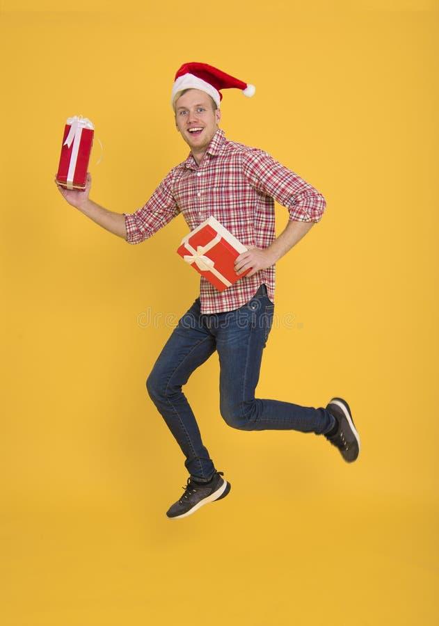 Knappe santahoed die van de mensenslijtage heel wat giftdoos op geel houden royalty-vrije stock foto