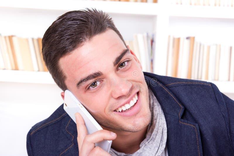 Knappe sexy mens die op telefoon het glimlachen spreken stock afbeeldingen