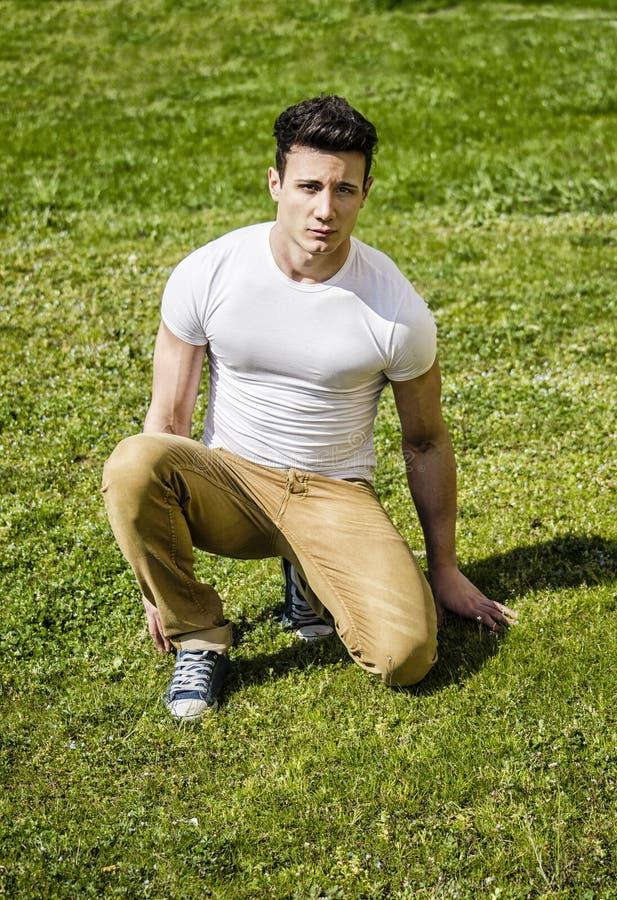 Knappe sexy mens in openlucht in het gras stock fotografie