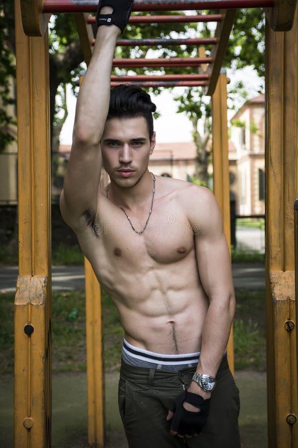 Knappe shirtless jonge mens die in openluchtgymnastiek in park uitoefenen royalty-vrije stock afbeelding