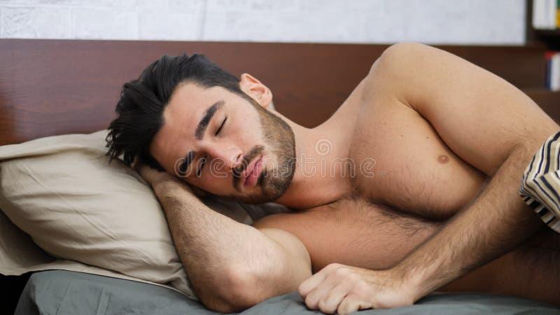 Knappe shirtless jonge mensenslaap in bed stock fotografie
