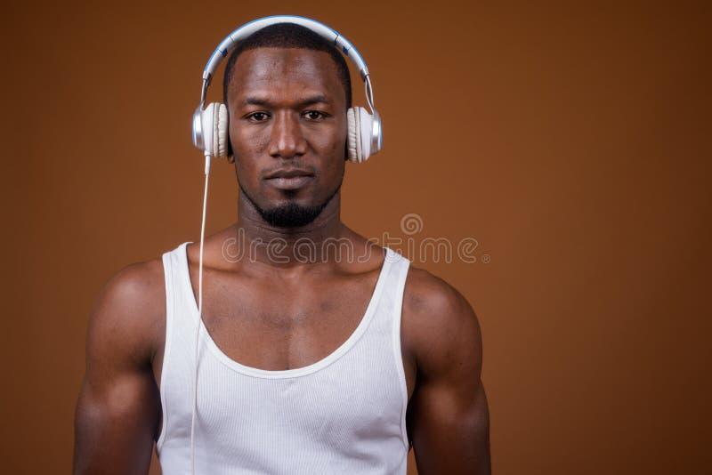 Knappe spier Afrikaanse mens die aan muziek tegen bruine B luisteren stock afbeeldingen