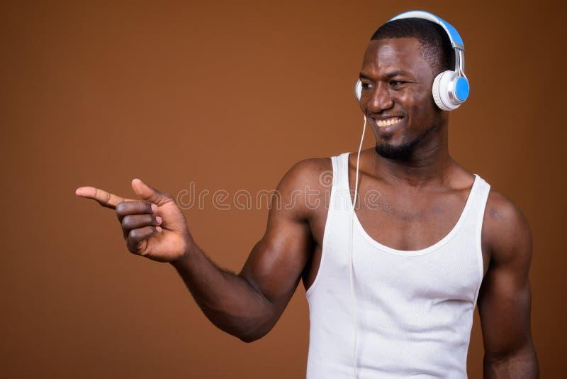 Knappe spier Afrikaanse mens die aan muziek tegen bruine B luisteren stock afbeelding