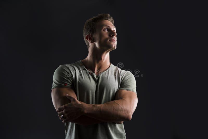 Knappe spier geschikte jonge mens die op donkere achtergrond omhoog kijken stock afbeelding