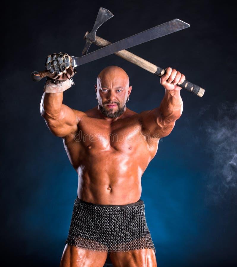 Knappe spier oude strijder met bijl en zwaard stock afbeeldingen