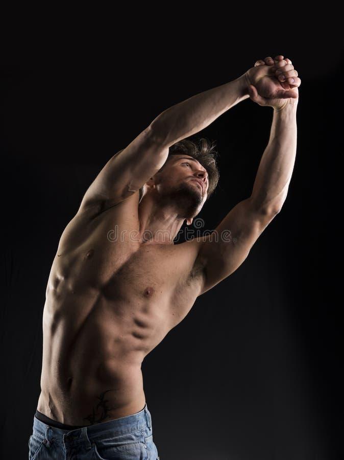 Knappe spier shirtless jonge en mens die zich omhoog uitrekken kijken royalty-vrije stock fotografie