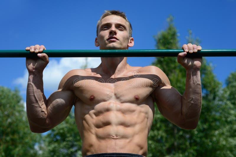 Knappe spierbodybuildermens die oefeningen in gymnastiek doen royalty-vrije stock afbeelding
