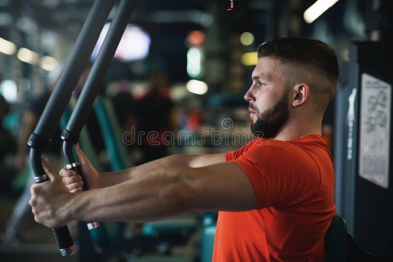 Knappe spiermens die hard bij gymnastiek uitwerken Borsttrainingen stock afbeeldingen