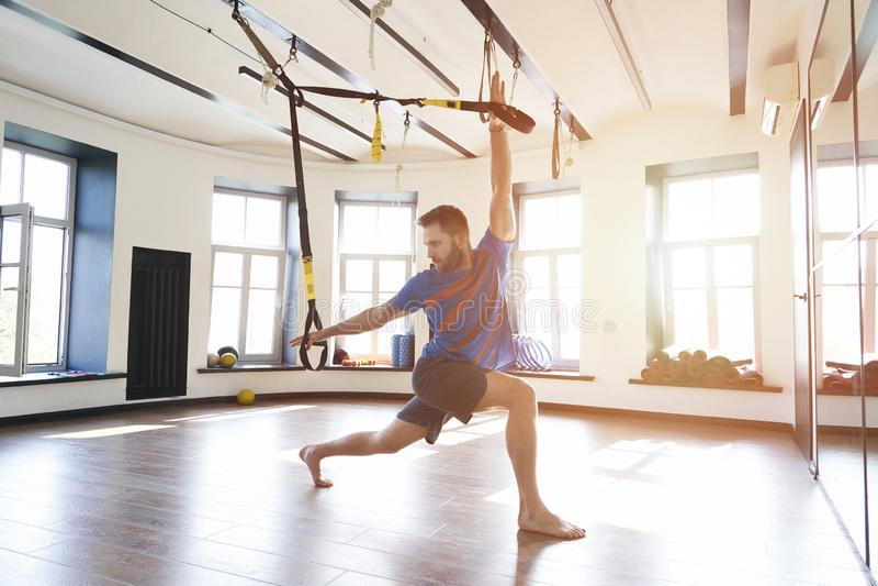 Knappe spiermensenatleet die oefening alleen met fitness riemen in moderne gymnastiekclub doen, training enige sport, zon het gla stock fotografie