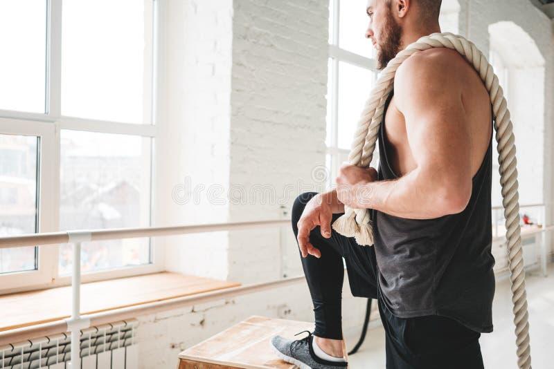 Knappe spiermensenholding op de training van de schouderkabel in lichte gymnastiek royalty-vrije stock fotografie