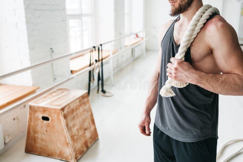 Knappe spiermensenholding op de training van de schouderkabel in lichte gymnastiek stock foto's