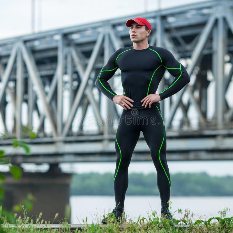 Knappe sportmens in sportkleding openlucht Actieve mannelijke buitenkant op de achtergrond van de brug stock foto's