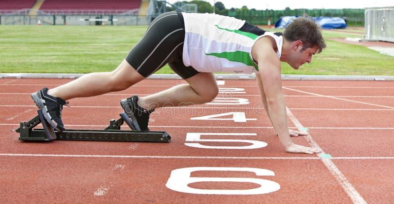 Knappe sprinter op de beginnende lijn in stadion royalty-vrije stock afbeeldingen