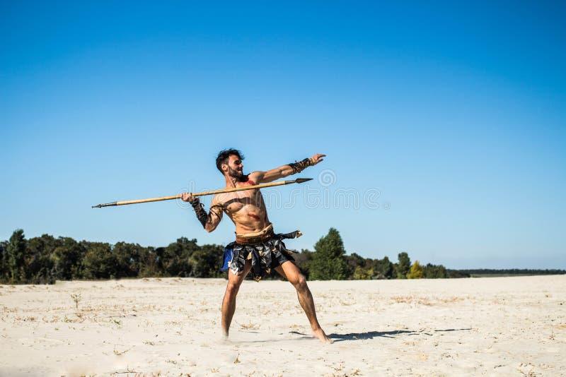 Knappe sterk bloodied Spartaans gooit spear stock fotografie