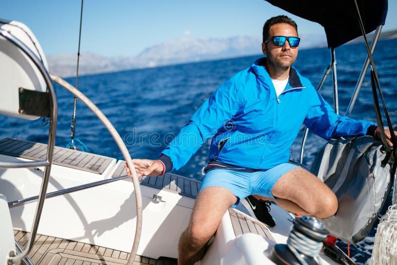 Knappe sterke mens die met zijn boot varen stock foto