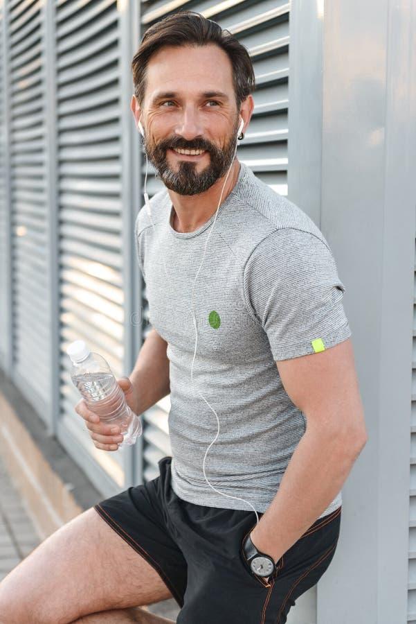 Knappe sterke rijpe sportman die met oortelefoons fles met water houden stock afbeelding