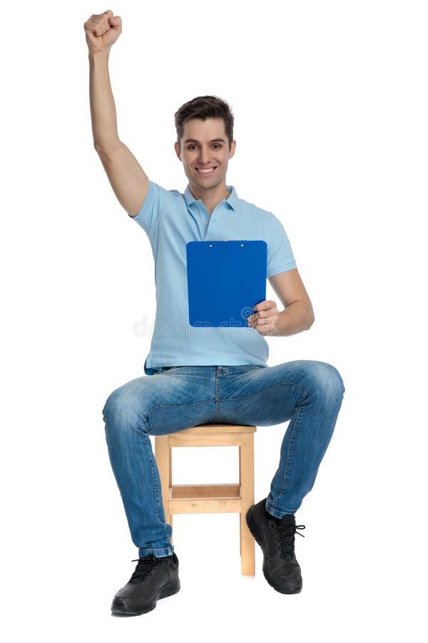 Knappe student die en een blauwe blocnote vieren houden stock afbeeldingen