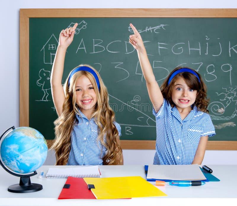 Knappe studenten die in klaslokaal hand opheffen stock fotografie
